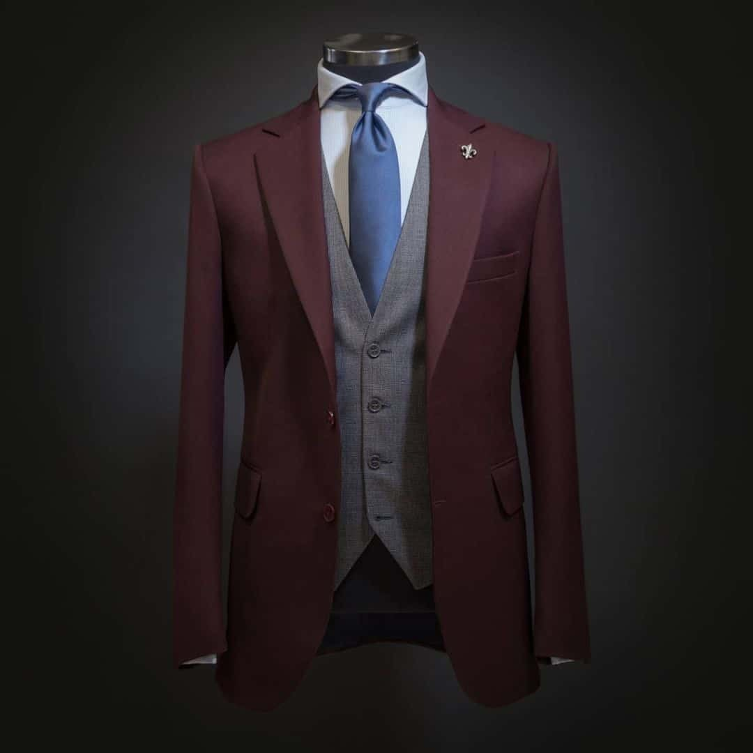 An image of an entire Suit setup from Signori in a burgundy colour, with grey elegant vest, white shirt and blue tie.