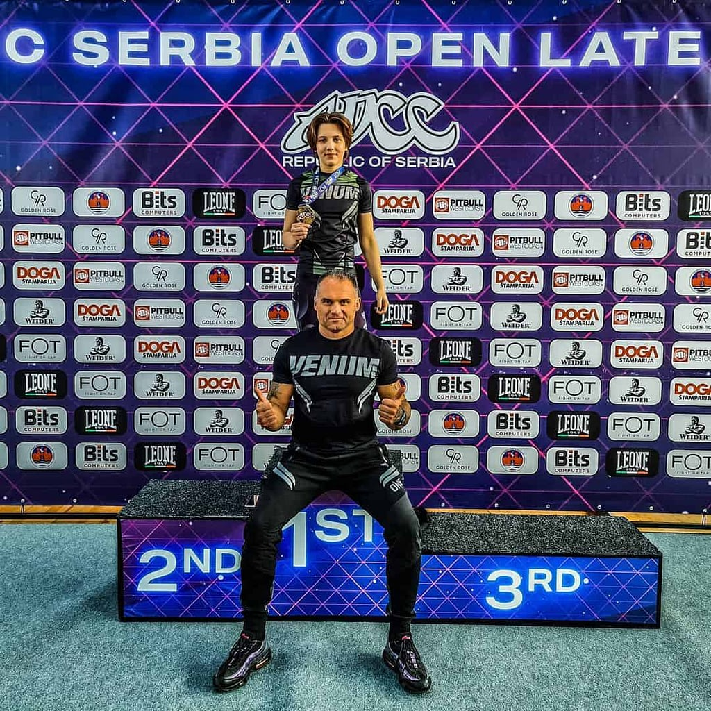 Ivica Aleksovski, with his daughter on a competition. He is wearing black venum t-shirt and he is sitting, while his daughter is standing behind him, with the medal in her hands.