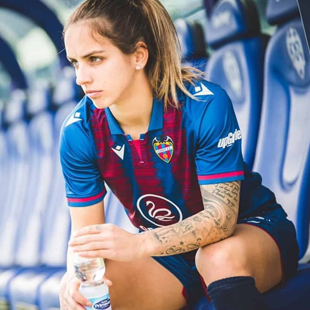 Natasa Andonova in a Levante jersey, staring furiously at the playing field while sitting on tribune and holding a bottle of water in her hands.