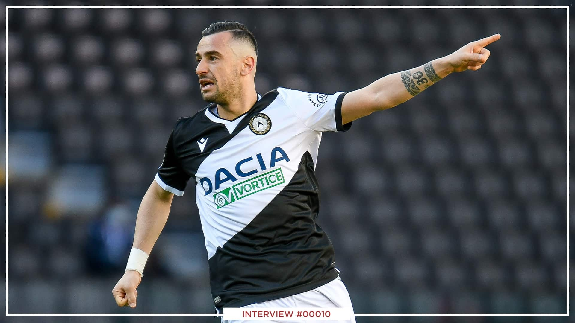 An image of Ilija Nestorovski, in a black football jersye with white details, and white shorts. He is pointing with his finder while running on the football playground.