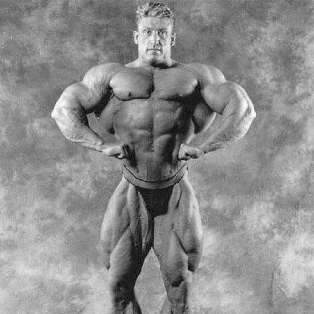 An image of Dorian Yates, on which he is flexing his muscles. The image is in black and white.