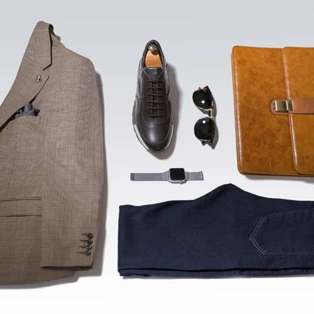 An image of light brown suite with grey handkerchief on it, together with dark blue jeans, black shoes, sunglasses, watch and light brown, leather bag. All those things on a white background.