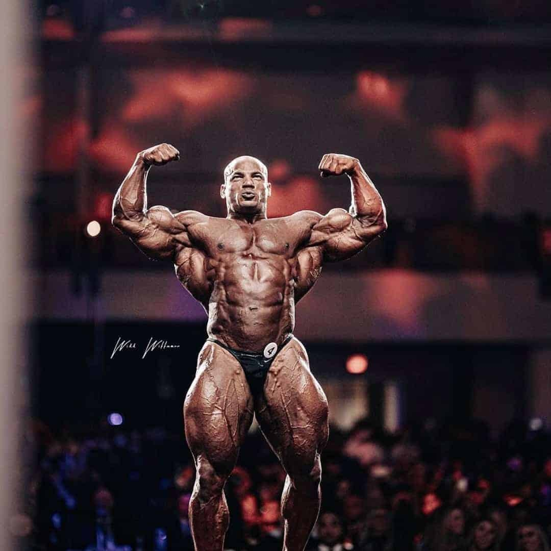 Big Ramy on the Mr. Olympia Stage while flexing his muscles.