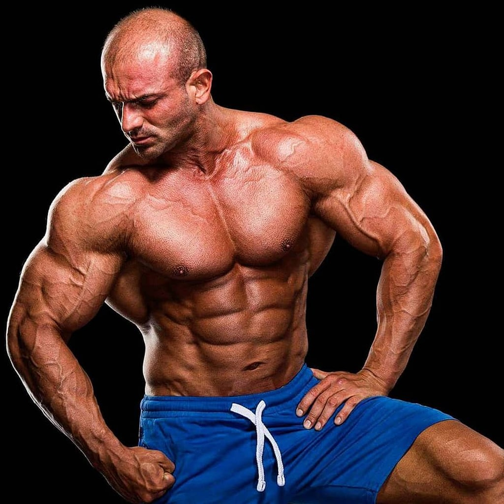 An image of Lepomir Bakic, a famous, professional bodybuilder. He is positioned in front of the camera, wearing blue sports shorts without a t-shirt. His head is set to the side, not looking at the camera. We can see his flexed muscles and veins.
