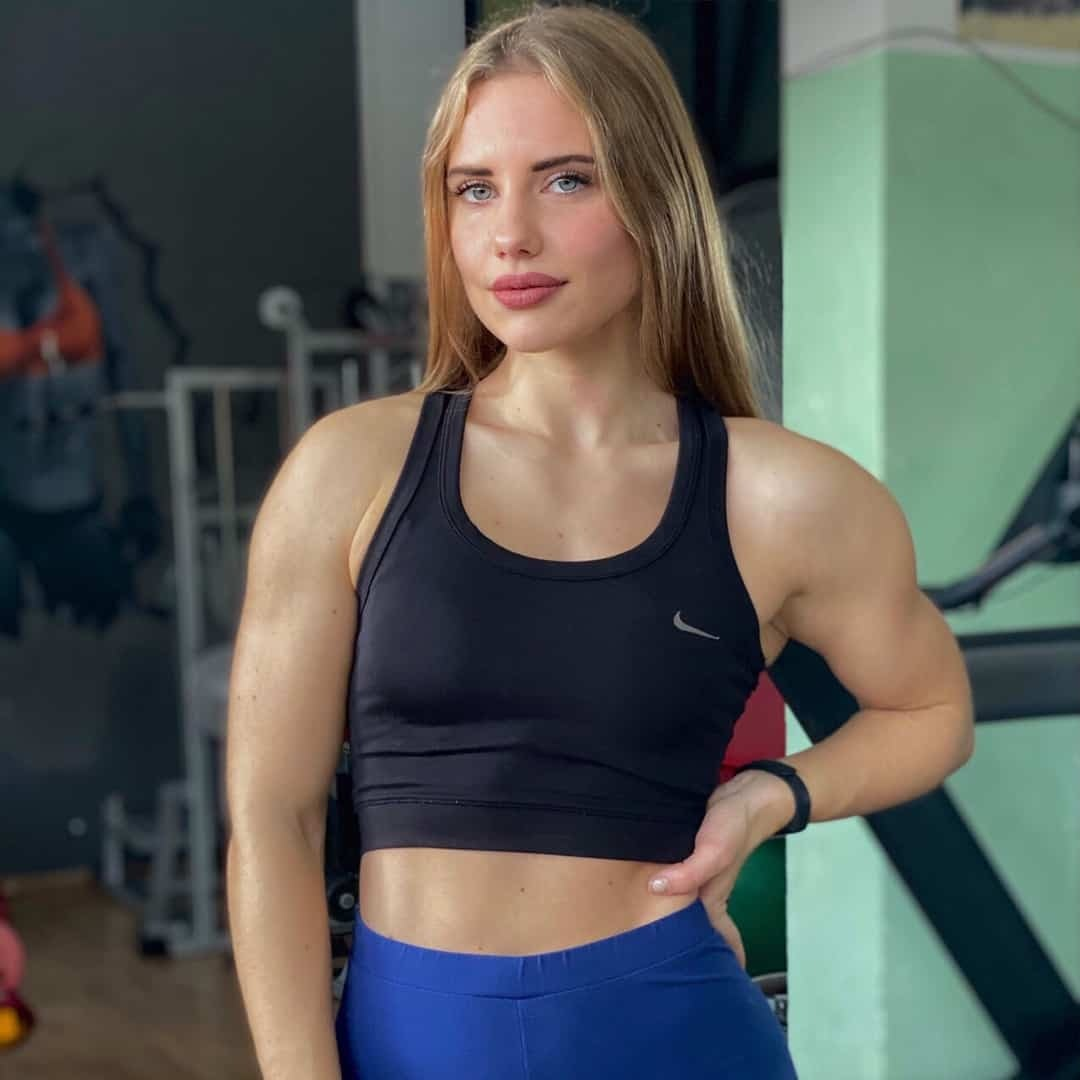 A photoshoot of Sara Stojanoska where she is staring straight at the camera, wearing navy blue sports bra and blue pants.
