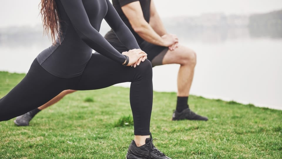 An image of a man and a woman stretching outside in the wilderness. Their face is not visible, the focus are their legs. The girl is wearing black leggings and the men is wearing black shorts.