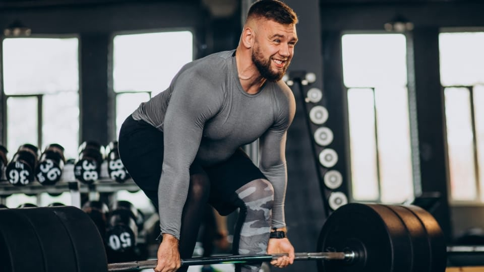 A person lifting way too much weight at the gym, while wearing grey sports t-shirt, and black leggings with grey details.