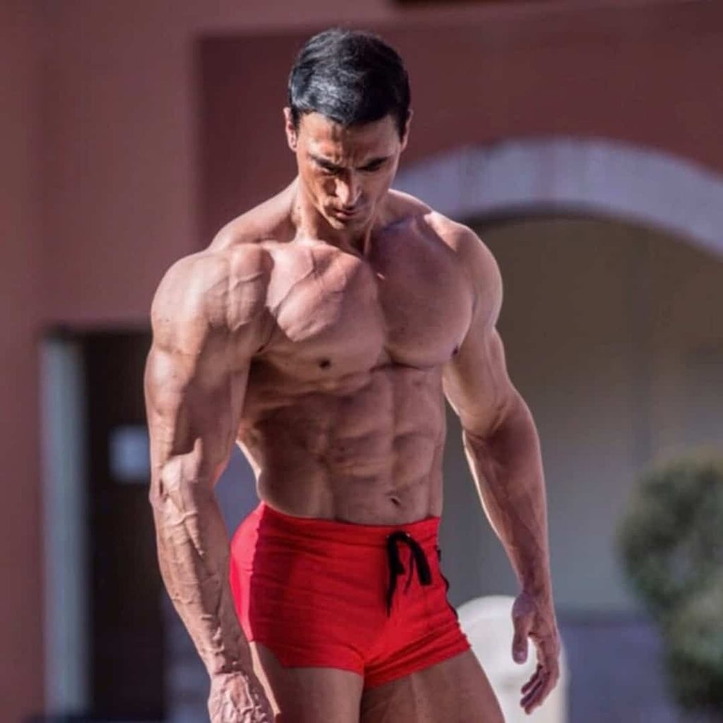 Branko Teodorovic staring at the ground in red pants as he is showcasing the build of his body