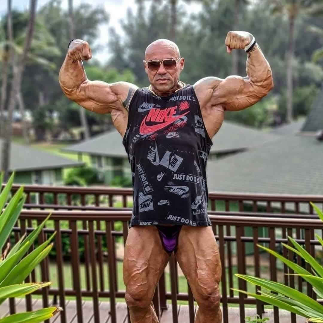 Tose Zafirov in a nike t-shirt, purple trunks, and sunglasses on his eyes. He is in a complex in Hawaii, near the beach, flexing his muscles.