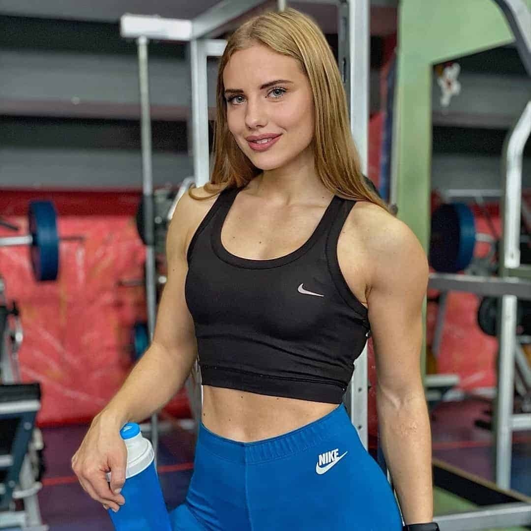 Sara Stojanoska smiling in front of a camera at the screen holding a blue bottle and wearing blue Nike pants.
