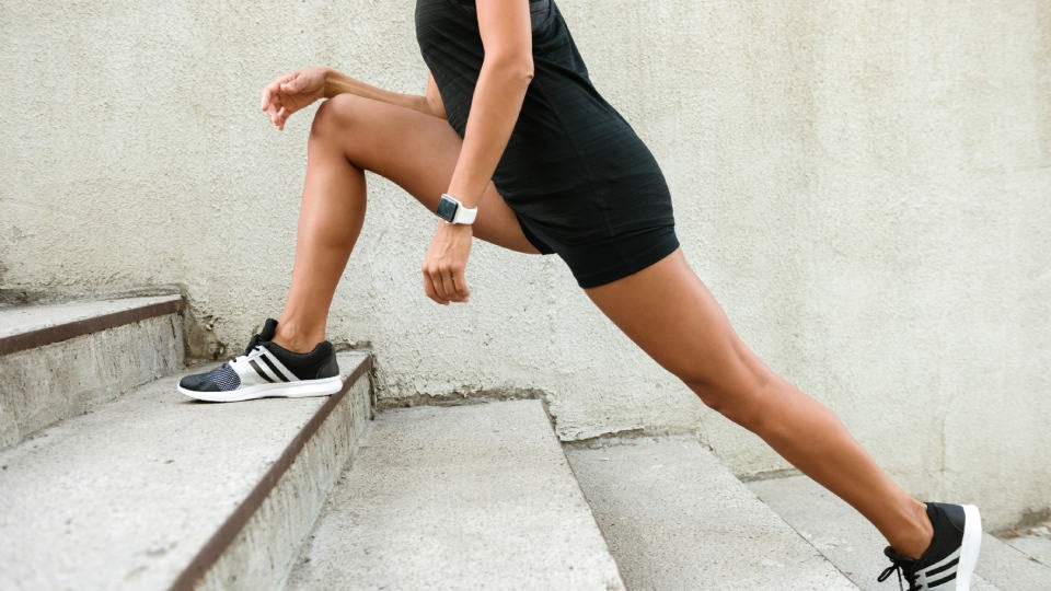 A women doing staircase climbing exercises. Her face is not visible, her legs are in the focus. She is wearing black shorts an black t-shirt.