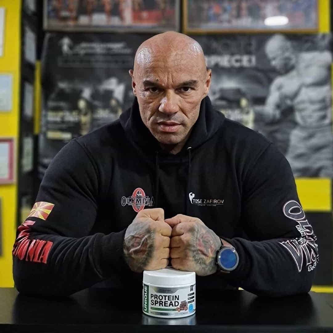 Tose Zafirov in a black Mr, Olympia hoodie, staring at the camera with his hands on a white box with protein spread.