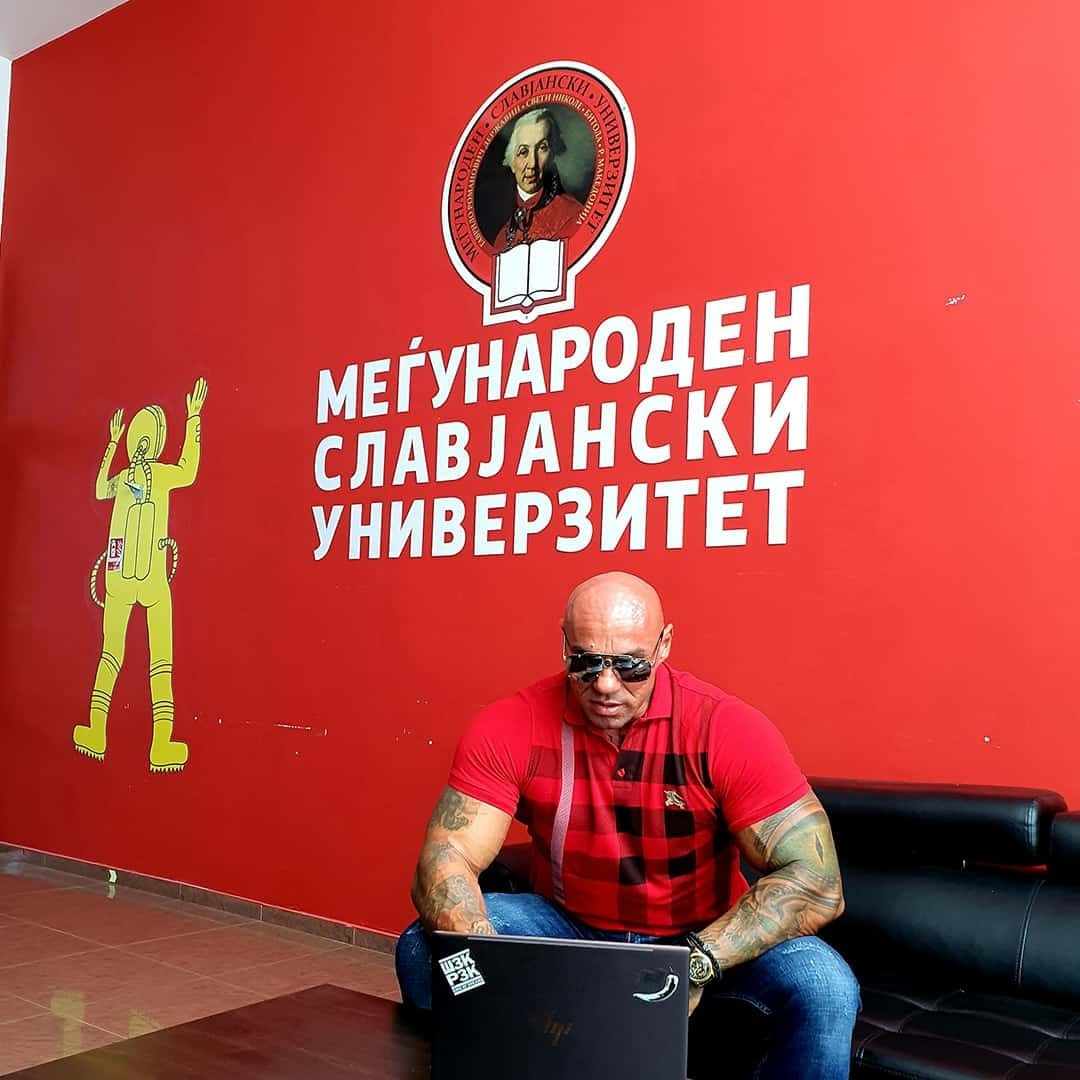 Tose Zafirov using his laptop at the International Slavic University G. R. Derzhavin. He is sitting on a black sofa, with sunglasses on his eyes, while wearing red t-shirt with black details. There is a red wall behind him with the logo of the International Slavic University.