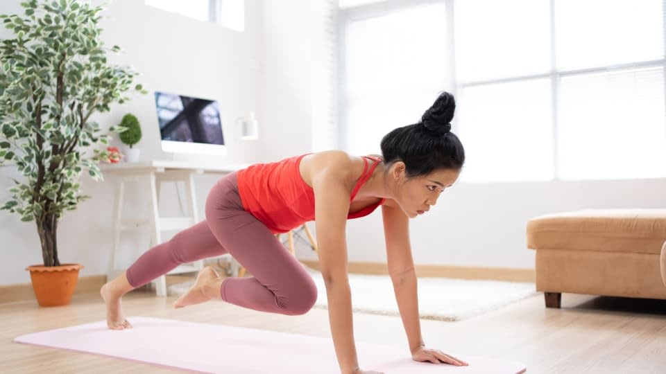 A woman training at home, doing mountain climbers while wearing red t-shirt and pink leggings
