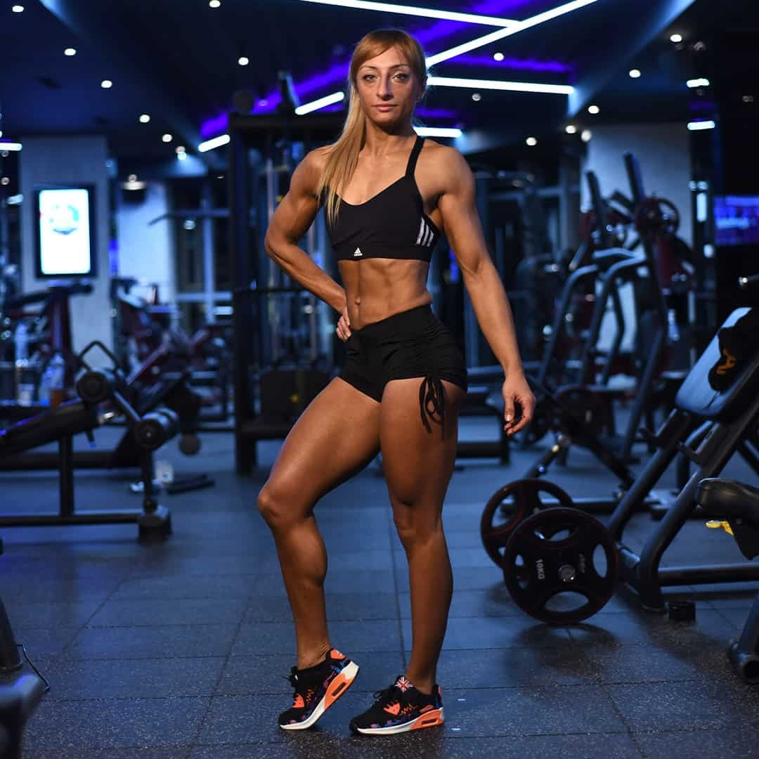 Gabriela Zafirova standing at a gym flexing her body's muscles, There is gym equipment behind her. She is wearing black adidas sports bra an black shorts.