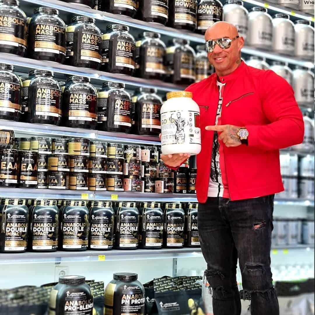 Tose Zafirov standing in front of a shelf with supplements from the Levrone Signature Series. He is wearing red jacket, grey jeans and sunglasses on his eyes, while holding protein and pointing with his finger to it.