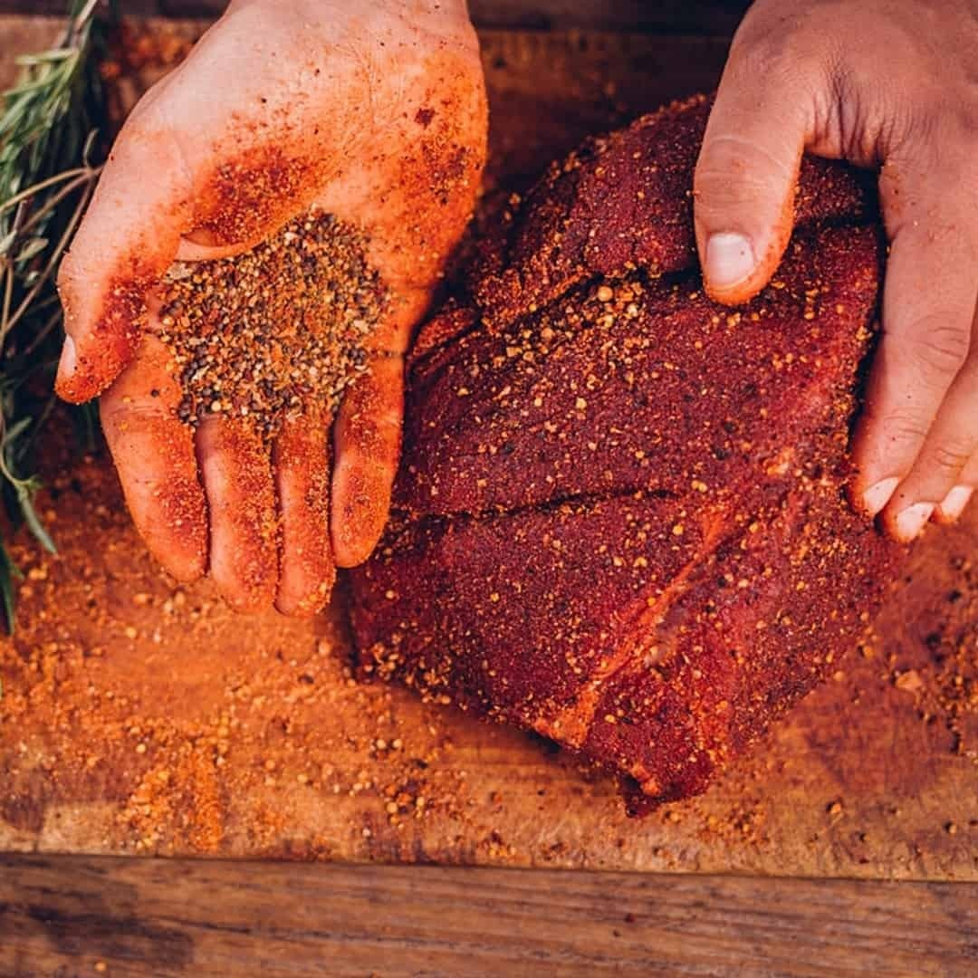 Hands of person salting and spicing meat