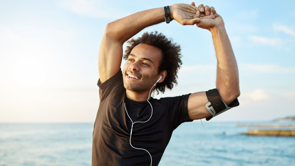 A person stretching before doing a workout, while listening to music on white headphones, preparing for exercise with music. He is wearing a black t-shirt. There is an ocean in the background.