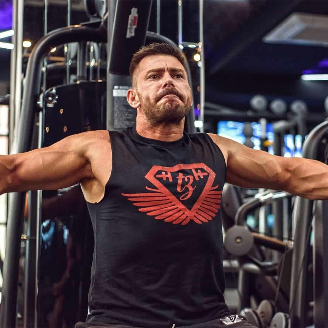 Trajche Stojanov training his chest in a gym on a machine specifically designed for that function. His face is mad and he is wearing black t-shirt with red details.