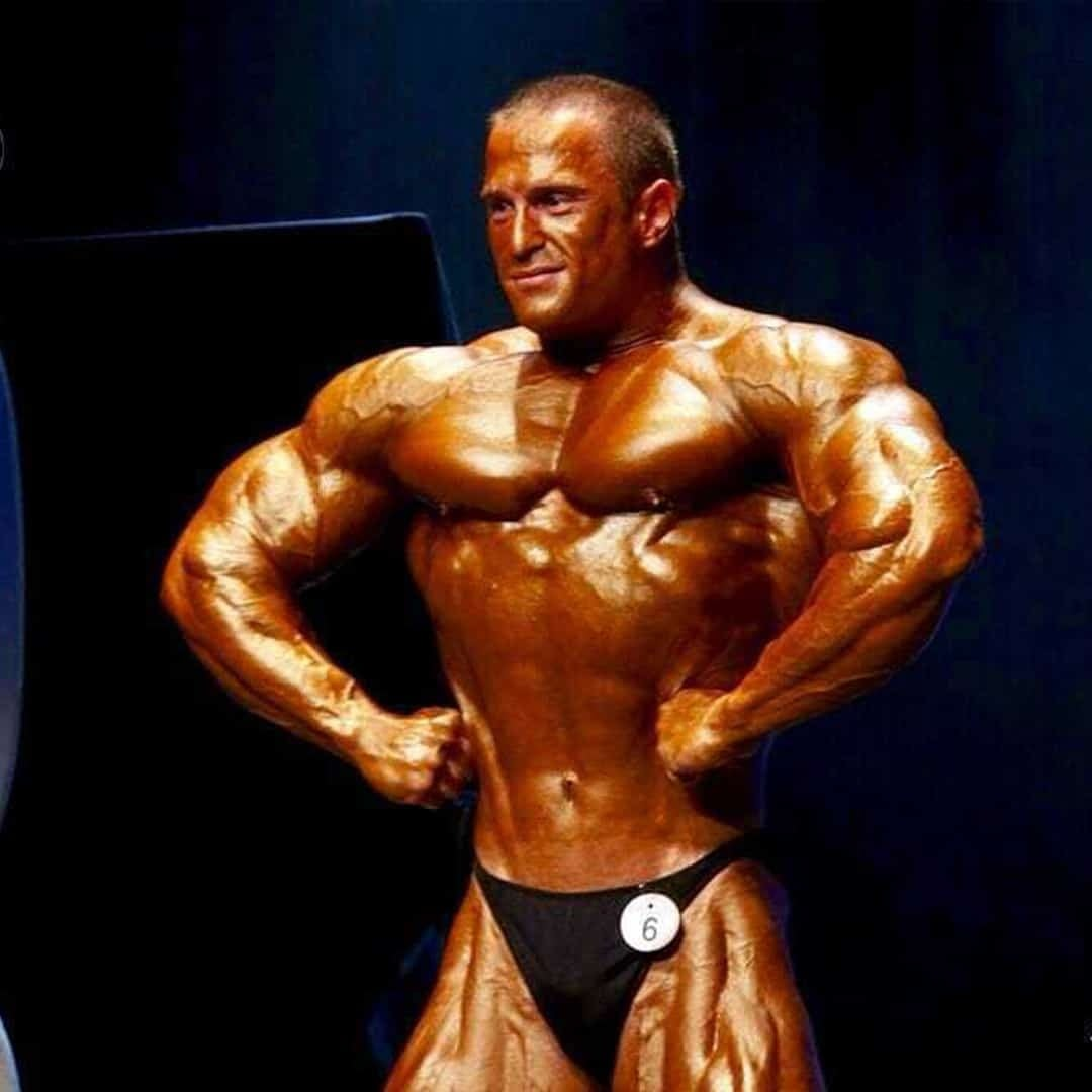 Ljubivoj Bakic flexing in front of the camera and staring at the audience at a competition with the number 6 showcased on his black trunks.