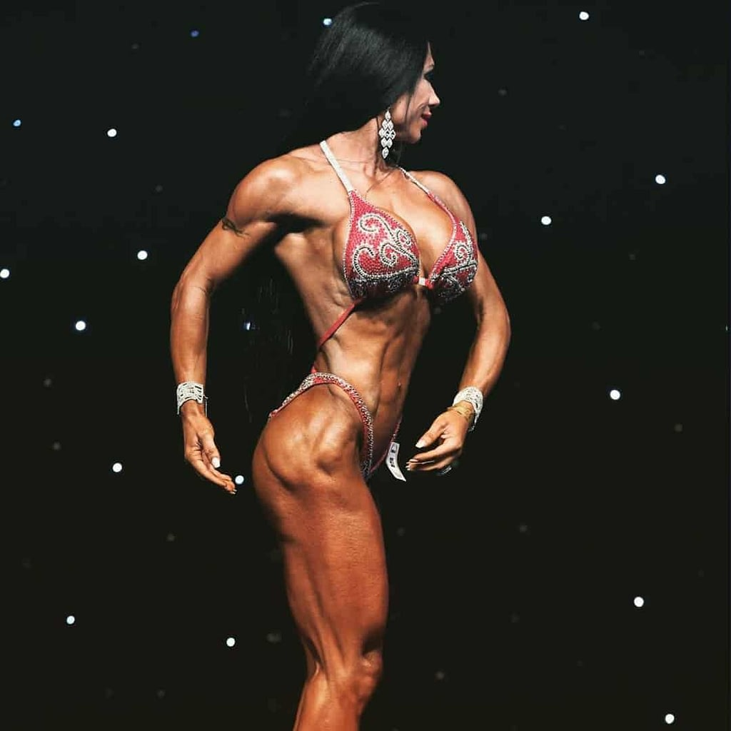 Maria Bozinovska on stage on a competition while flexing her muscles. She is wearing elegant red bikini set.