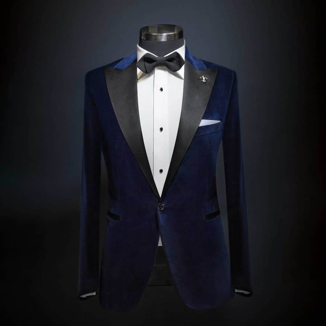 An image of an entire Suit setup from Signori in navy Blue in the form of a Tuxedo, with white shirt and black bow tie.