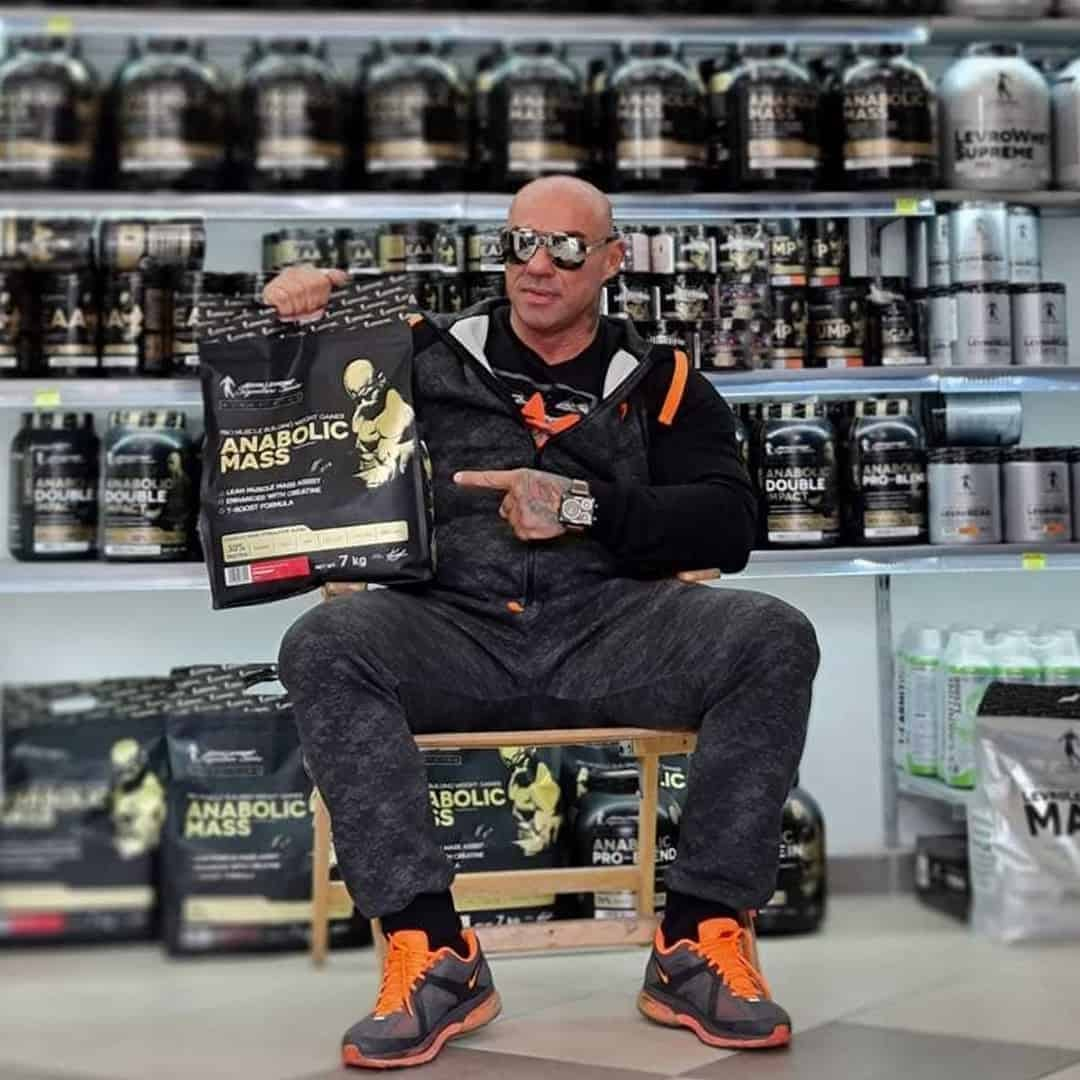 Tose afriov on a dark grey tracksuit, with orange detials and sunglasses on his eyes. He is sitting in front of a shelf with supplements from the Levrone Series. He is holding anabolic mass from the black line in his hand,