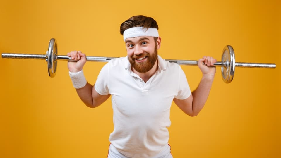 A person not lifting enough weight smiling at the camera with white clothes and a yellow background