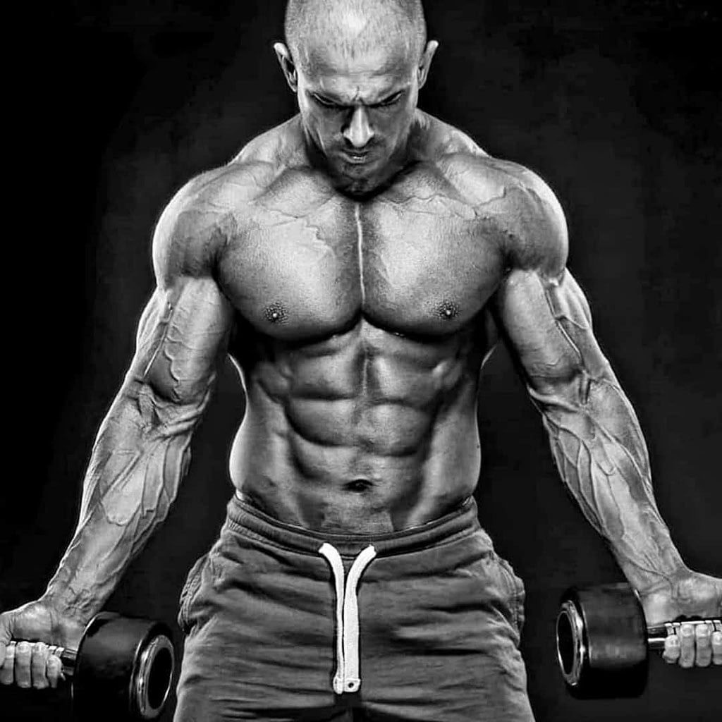 An black and white image of Lepomir Bakic, a famous bodybuilder. He is holding weights in both hands, flexing his muscles. He is positioned right in front of the camera, shirtless. Lepomir is looking down, not in the camera.