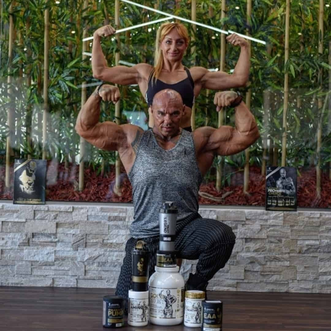 An image of Tose Zafirov and his wife Gabriela Zafirova flexing their biceps muscles. There are product from the Levrone Signature Series in front of them and a wall with plastic bamboos behind them. Tose is wearing grey t-shirt and Gabriela is wearing black sports bra.