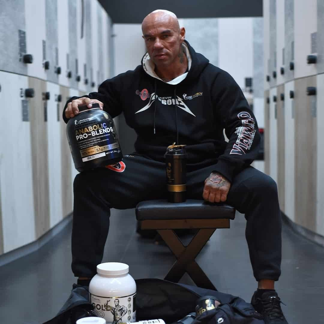 Tose Zafirov in a gym fitting room, sitting and staring at the camera, while holding some supplements from Kevin Levrone. He is wearing black Mr. Olympia tracksuit.