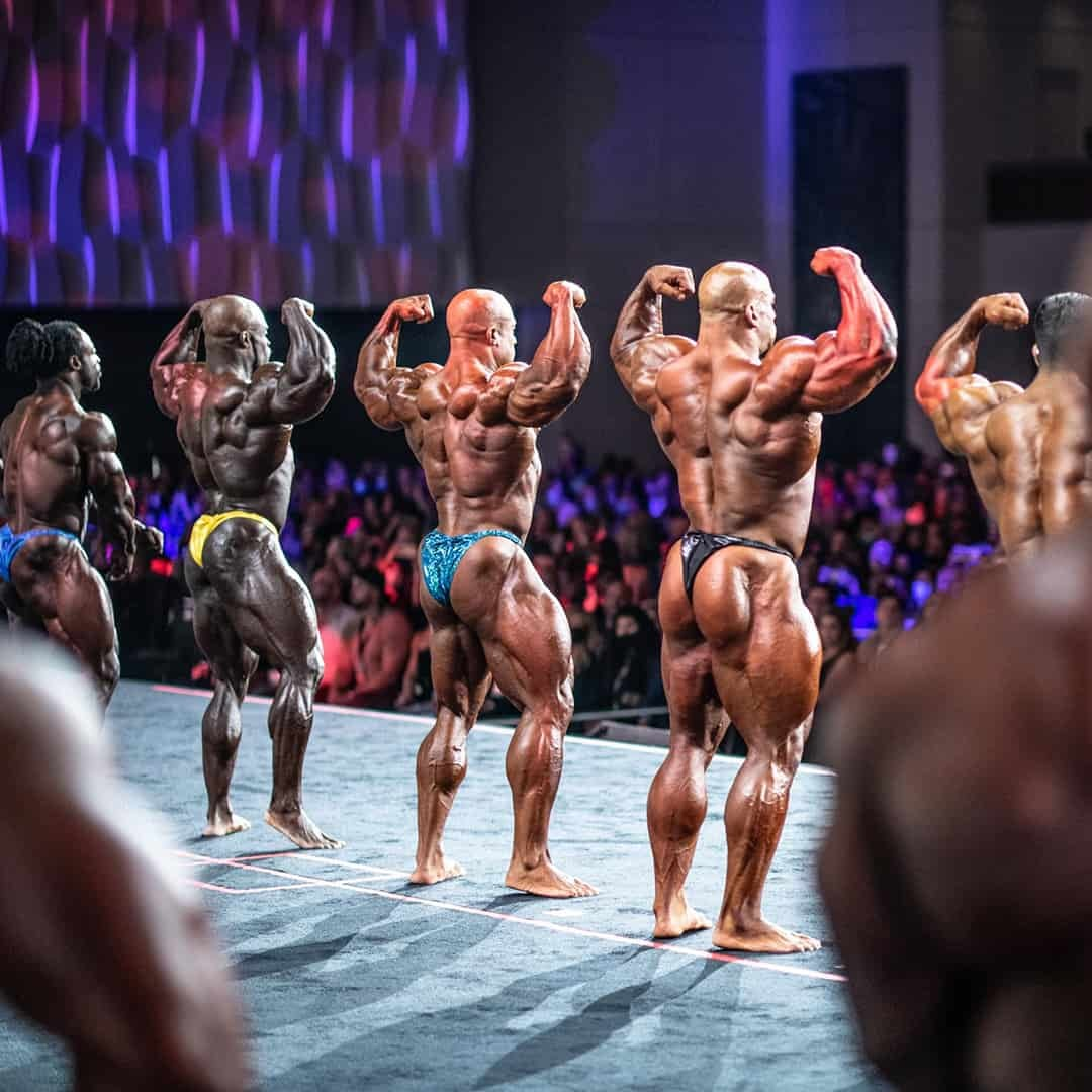 An image of the bodybuilding competitors, on the Stage of Mr. Oympia. They are turned with their back in the front of the camera.