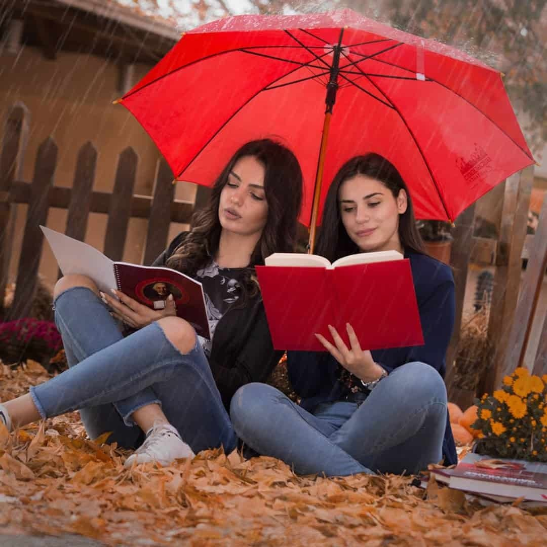 Two women sitting in the ground on a rainy day under a red umbrella, reading about International Slavic University G. R. Derzhavin. They are wearing jackets and jeans.