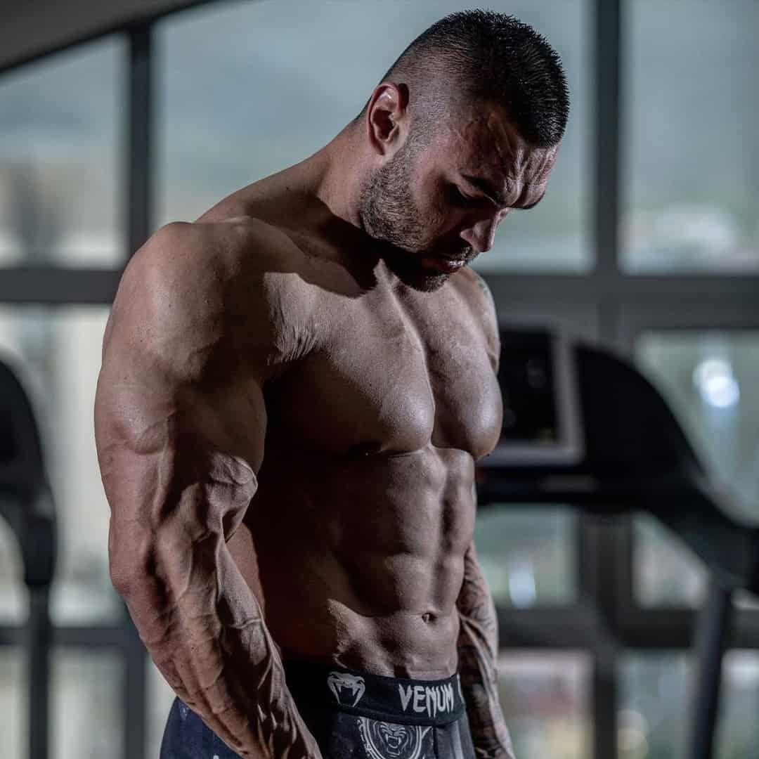 Hristijan Manasievski staring at the floor and has all of this muscles fully flexed where we can see the outline of his entire body in a darker room.