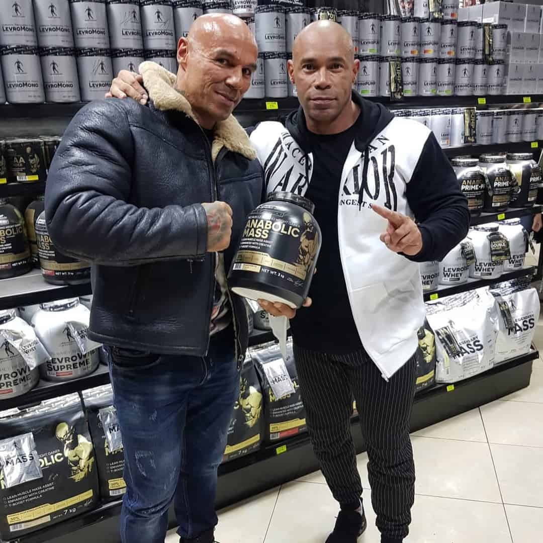 Tose Zafirov and Kevin Levrone, with a shelf of proteins in the background, Kevin is hugging Tose while he is holding protein in his hands.