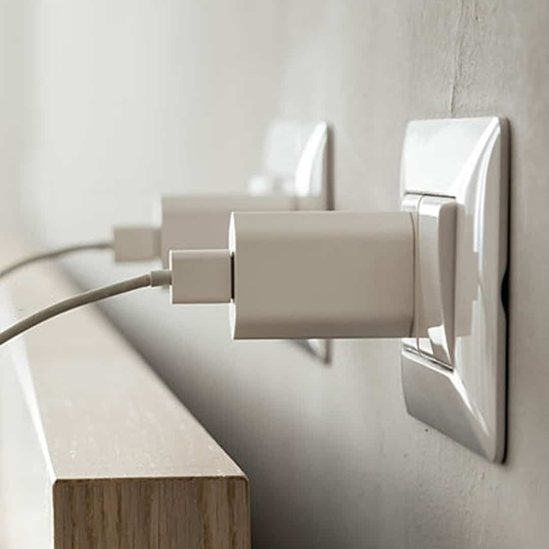 white smartphone charger connected to a socket
