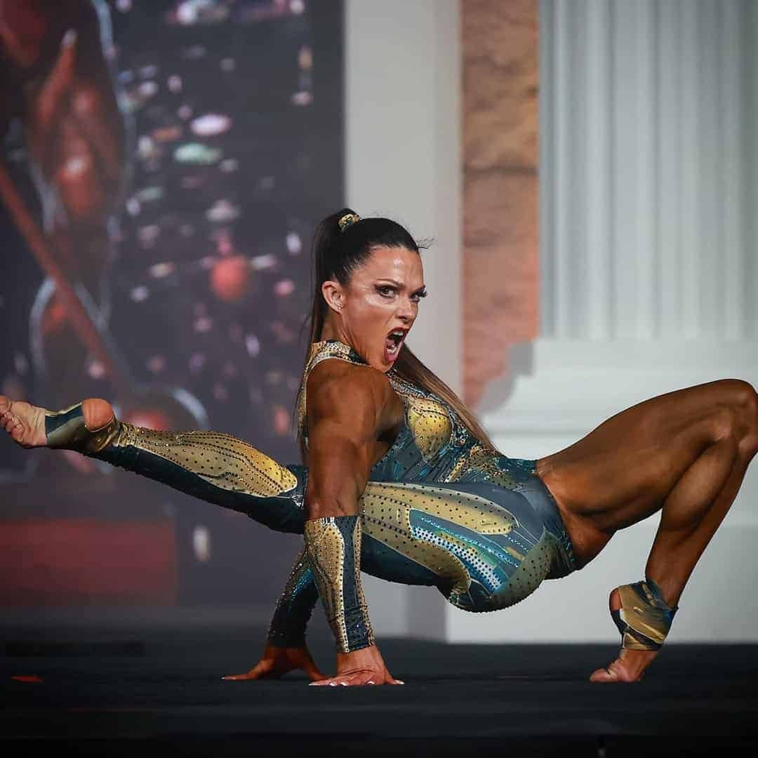 An image of Oksana Grishina, while performing on Mr. Olympia stage in an elegant dark green costume with gold details.