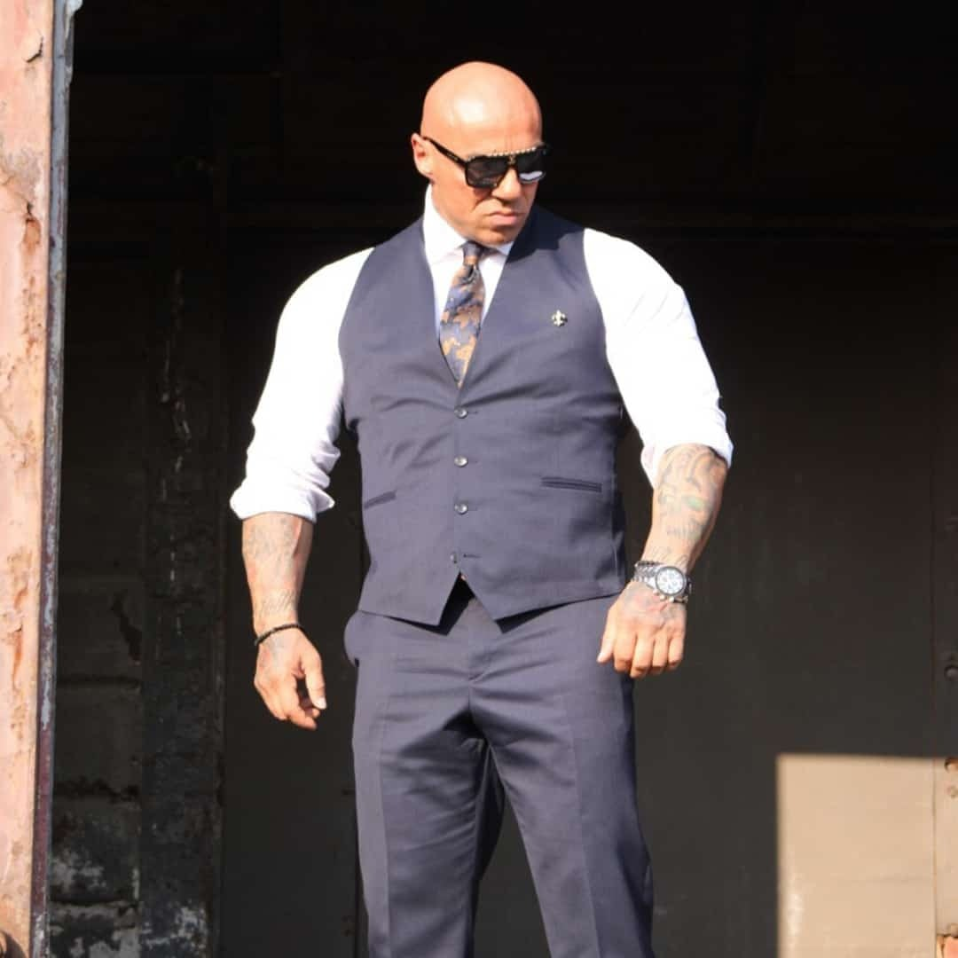 An image of Tose Zafirov wearing a white shirt and vest in a navy blue from Signori at a train station. He is also wearing a sunglasses on his eyes.