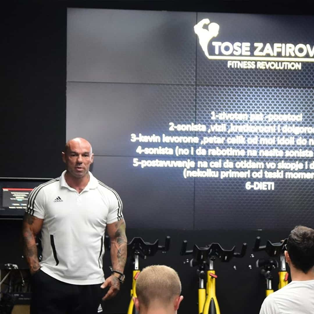 Tose Zafirov presenting at the Fit Biz Academy in front of students. He is wearing white, adidas t-shirt and black sweatpants. There is a huge screen behind him, with a text and his logo.