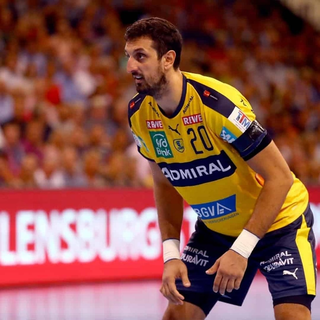 Ilija Abutovic in a yellow jersey. He is preparing to strike or receive the ball throughout a handball tournament