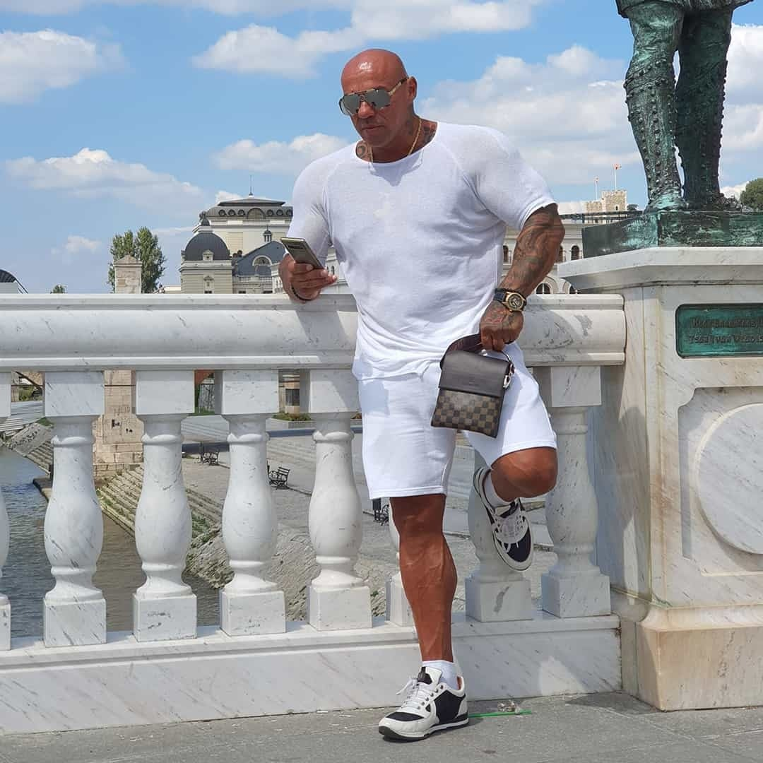 Tose Zafirov in a white shirt and white shorts, and brown men bag standing on a bridge. He is wearing sunglasses on his eyes, and he is holding a smartphone in his hands