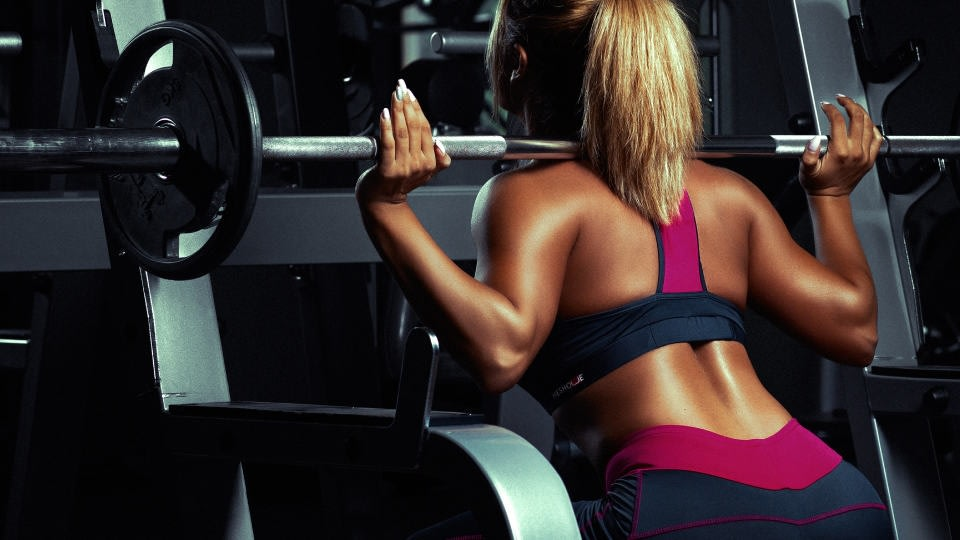 A woman with blonde hair doing squats too at the gym. She is turned with her back in front of the camera while wearing dark grey with dark pink sports bra and leggings.