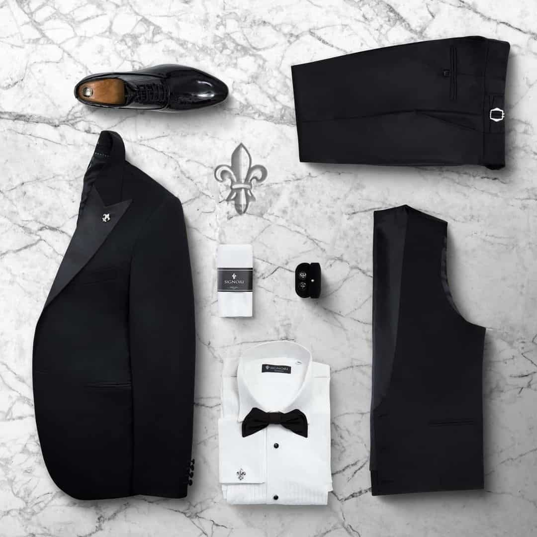An image of an entire Suit setup from Signori in black, with a white shirt and black bow tie. There are some elegant, black shoes too.