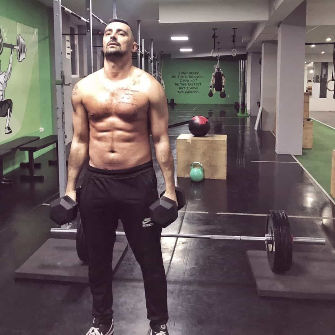 Aleksandar Mandzukovski shirtless at the gym training his abs. There is gym equipment in the background.