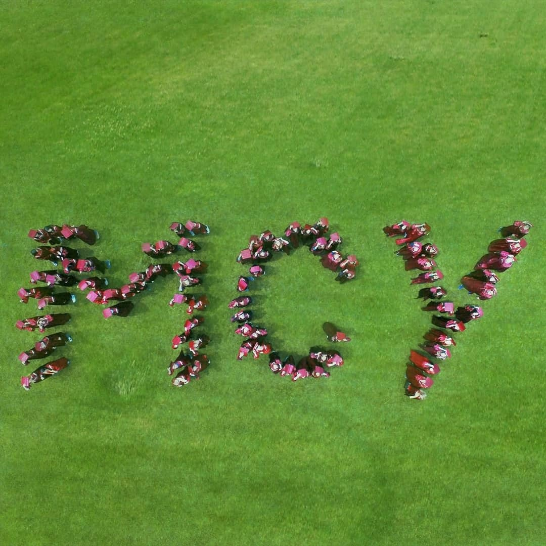 A green ground with letters ''MCY'' made from students who just graduated, standing on the ground.