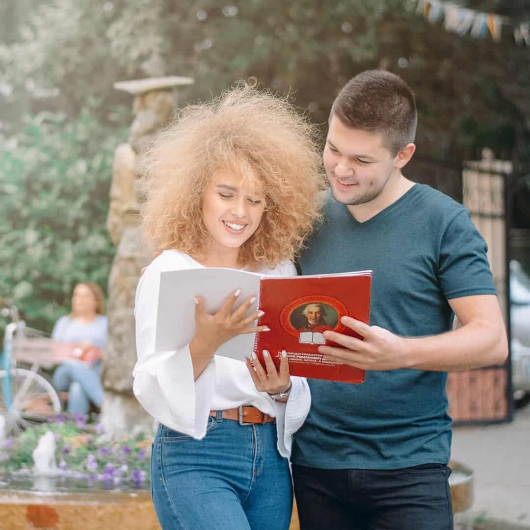 A man and a woman reading about the International Slavic University G. R. Derzhavin, while standing one to another and smiling. The blondie is wearing white shirt and jeans while the boy is wearing blue t-shirt and black trousers.