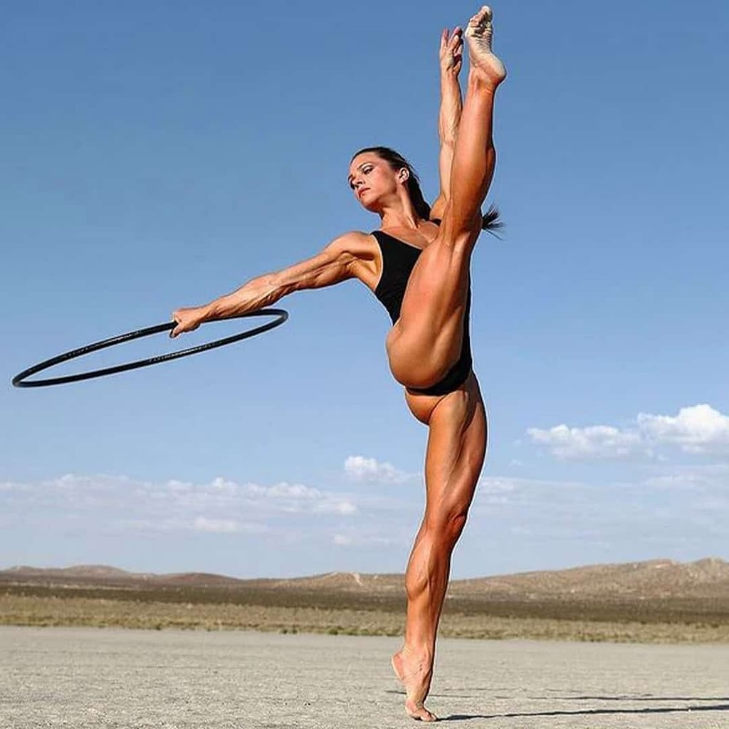 Oksana Grishina doing gymnastic poses and flexing her muscles on a road, with some hills in the backgound.