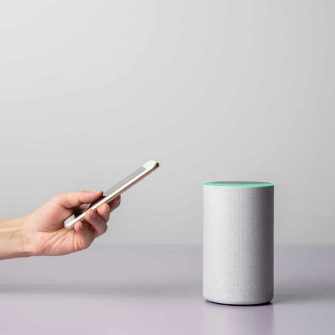 An image of a hand holding a white smartphone, next to a white, smart speaker, on a white background