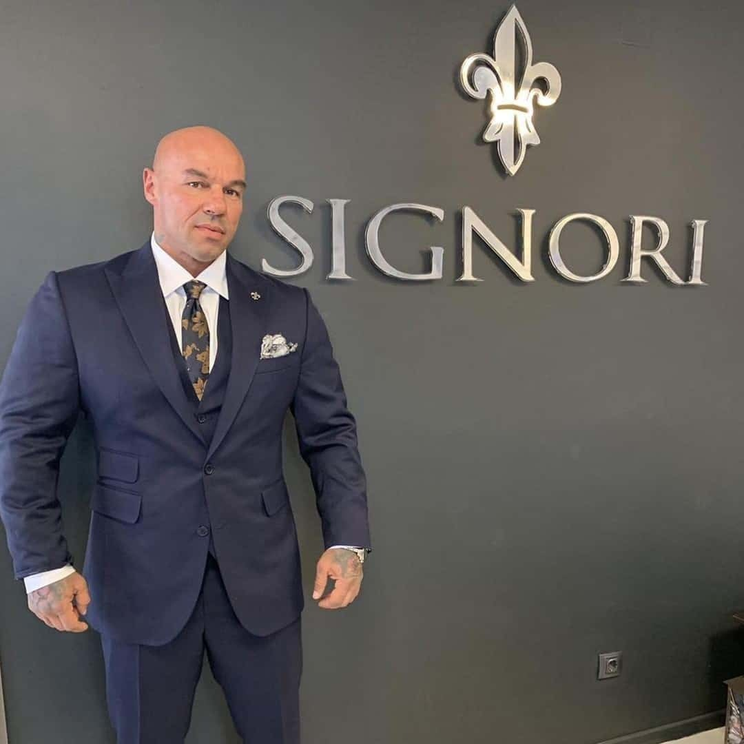 An image of Tose Zafirov wearing a suit from Signori in a navy blue colour, staying in front of a grey wall with Signori logo on it.