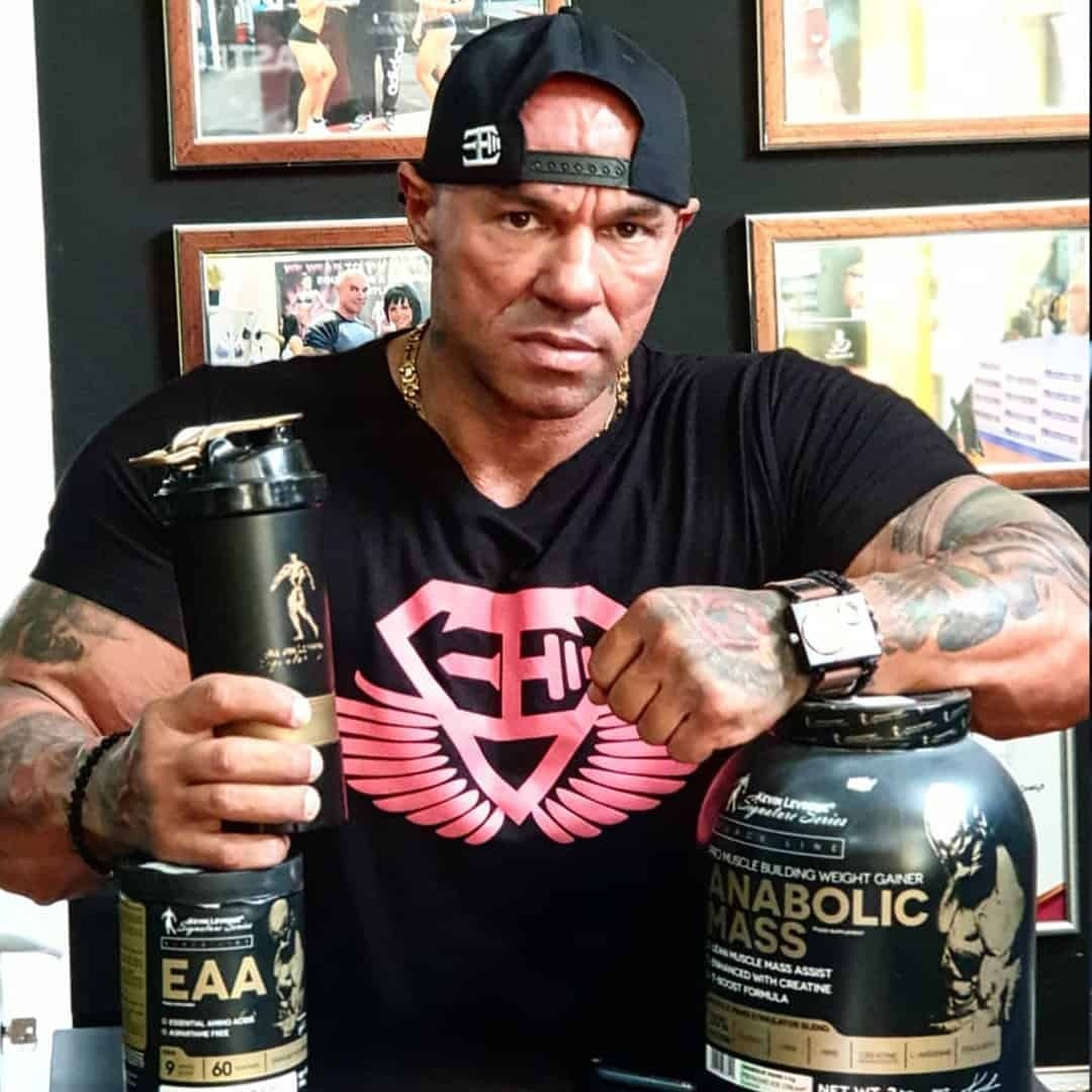 Tose Zafirov in a black t-shirt with red logo on it, and a black cap, with some product from the Kevin Levrone Signature Series.